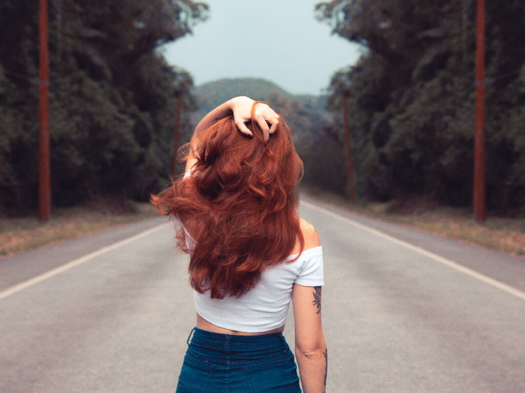Girl walking on a highway, from her back